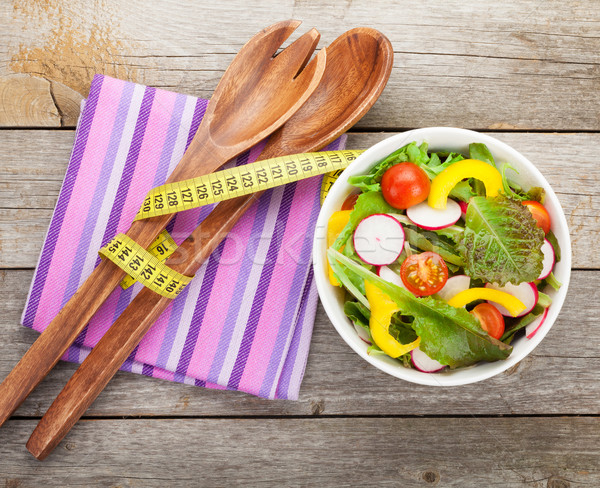 Fresh healthy salad on wooden table and kitchen utensil Stock photo © karandaev