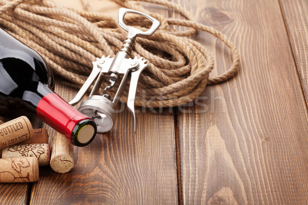 Red wine bottle, corks and corkscrew over wooden table backgroun Stock photo © karandaev