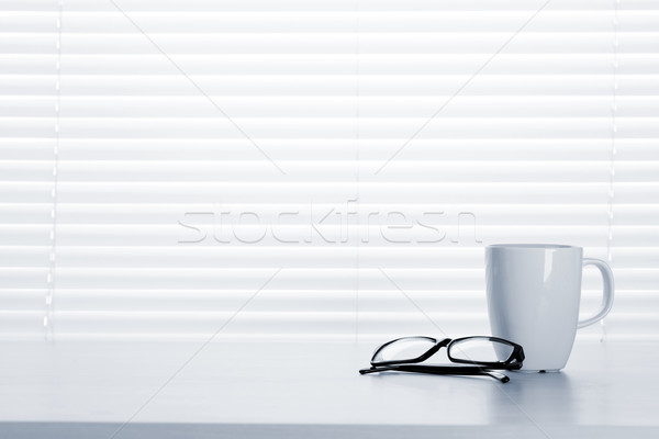 Office desk workplace with coffee cup and glasses Stock photo © karandaev
