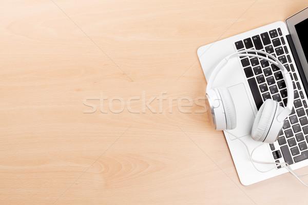 Headphones over laptop on wooden desk table Stock photo © karandaev