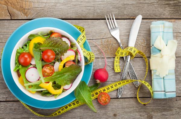 Fresh healthy salad and measuring tape. Healthy food Stock photo © karandaev