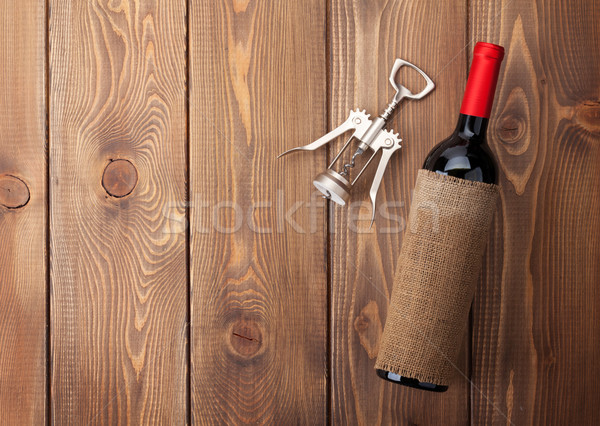 Red wine bottle and corkscrew on wooden table Stock photo © karandaev