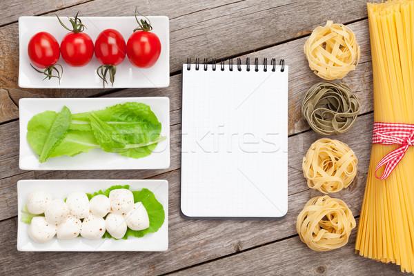 Tomatoes, mozzarella, pasta and green salad leaves with notepad  Stock photo © karandaev