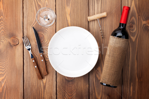 Table setting with empty plate, wine glass and red wine bottle Stock photo © karandaev