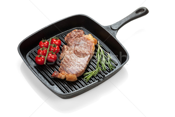 Sirloin steak with rosemary and cherry tomatoes cooking in a fry Stock photo © karandaev