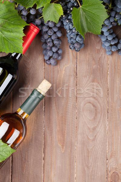 Red grape and wine bottles Stock photo © karandaev