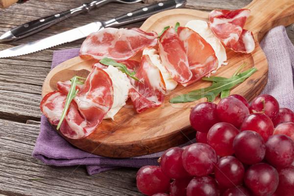 Prosciutto mozzarella vágódeszka fa asztal étel levél Stock fotó © karandaev