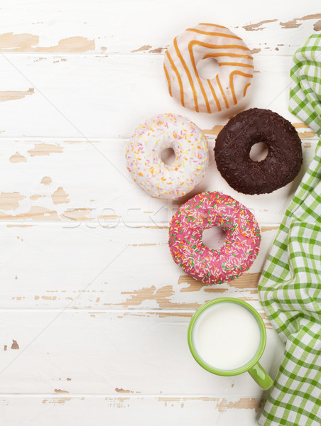 Milk and donuts on wooden table Stock photo © karandaev