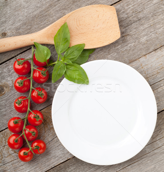 Empty plate on wooden with tomatoes and utensil Stock photo © karandaev