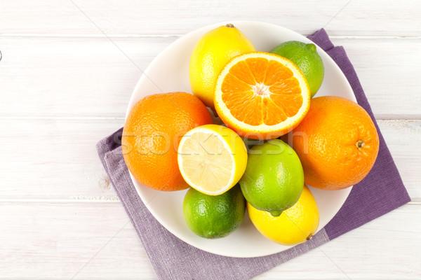 Citrus fruits on plate. Oranges, limes and lemons Stock photo © karandaev