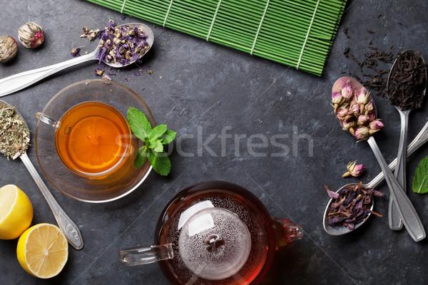 Tea cup, teapot and assortment of dry tea in spoons Stock photo © karandaev