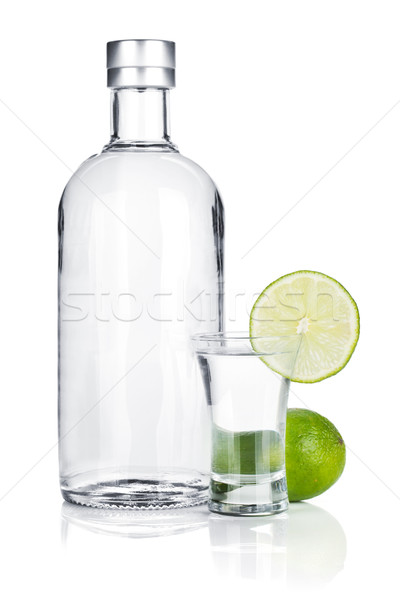 Bottle of vodka and shot glass with lime slice Stock photo © karandaev