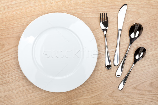 üres fehér tányér ezüst étkészlet fa asztal felülnézet Stock fotó © karandaev