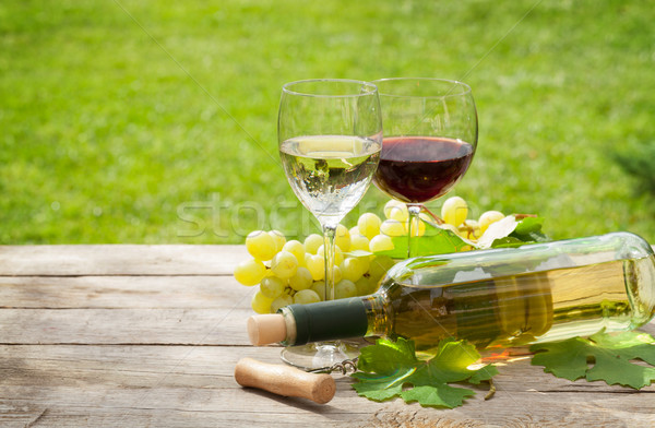 White and red wine glasses and bottle with bunch of grapes Stock photo © karandaev