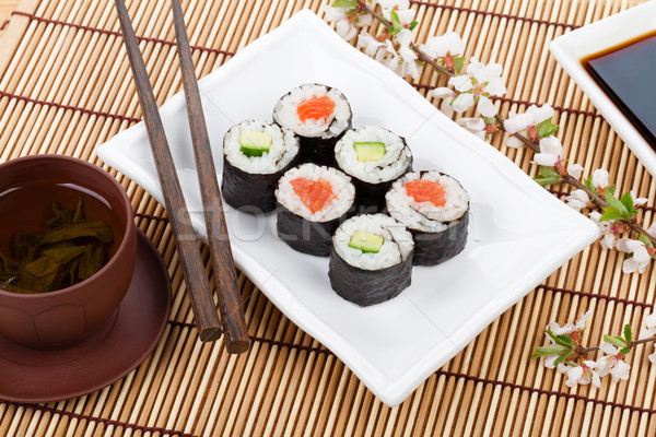 Stock photo: Sushi maki set, green tea and sakura branch