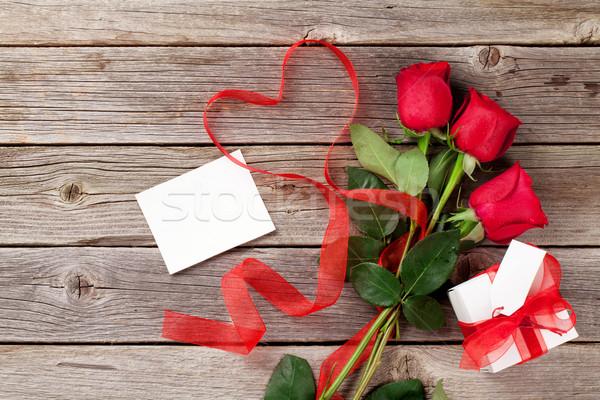 Foto stock: Rosas · rojas · caja · de · regalo · forma · de · corazón · cinta · madera · mesa · de · madera