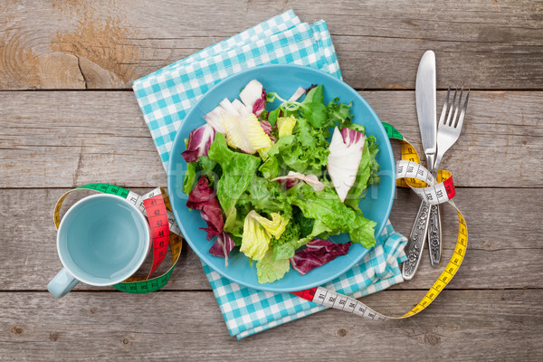 Plate with fresh salad, measure tape, cup, knife and fork. Diet  Stock photo © karandaev