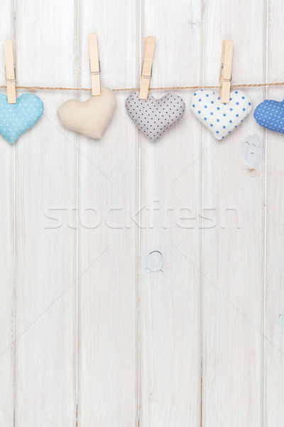 Valentines day toy hearts hanging on rope over white wooden back Stock photo © karandaev