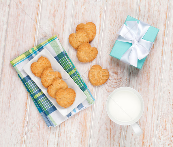 Cup of milk, heart shaped cookies and gift box Stock photo © karandaev