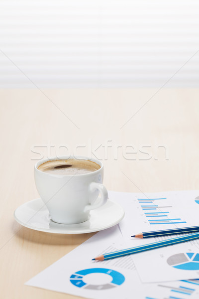 Office desk workplace with coffee and charts Stock photo © karandaev