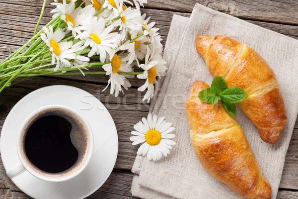 Croissantok kávéscsésze kamilla virágok virágcsokor fa asztal Stock fotó © karandaev