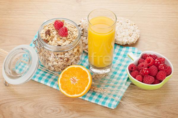 Sani colazione muesli frutti di bosco succo d'arancia tavolo in legno Foto d'archivio © karandaev