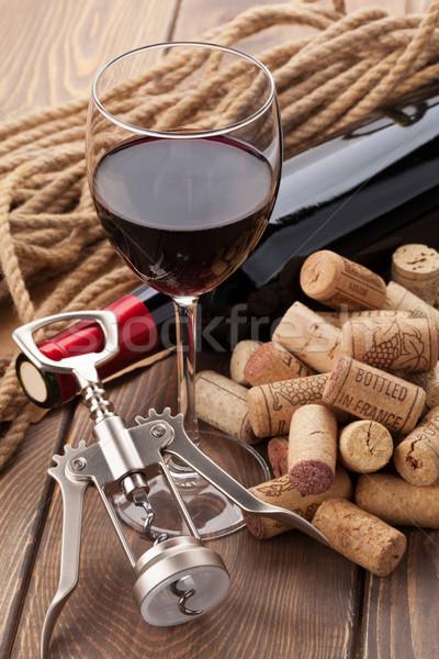 Glass of red wine, bottle, heap of corks and corkscrew Stock photo © karandaev