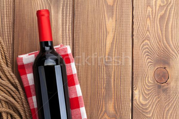 Red wine bottle over towel on wooden table Stock photo © karandaev