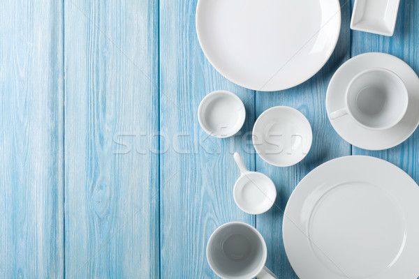Empty plates and bowls on blue wooden background Stock photo © karandaev