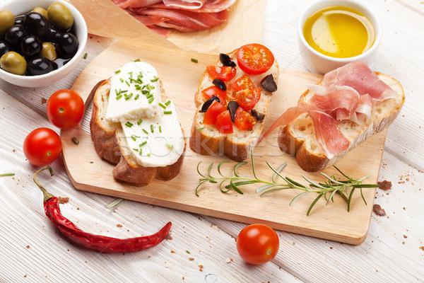 Bruschetta sajt paradicsomok prosciutto vágódeszka étel Stock fotó © karandaev