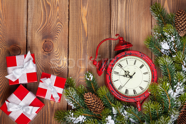 Christmas clock over wooden background with snow fir tree and gi Stock photo © karandaev