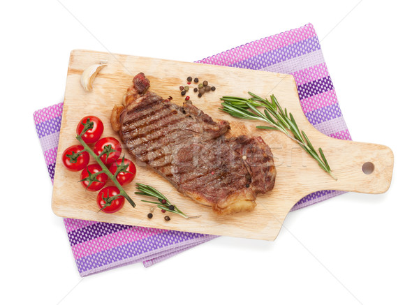 Sirloin steak with rosemary and cherry tomatoes on a cutting boa Stock photo © karandaev