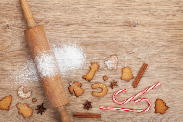 Rolling pin with flour, spices and cookies on wooden table Stock photo © karandaev