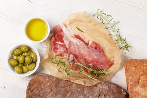 Olasz prosciutto olajbogyók fehér fa asztal kenyér Stock fotó © karandaev