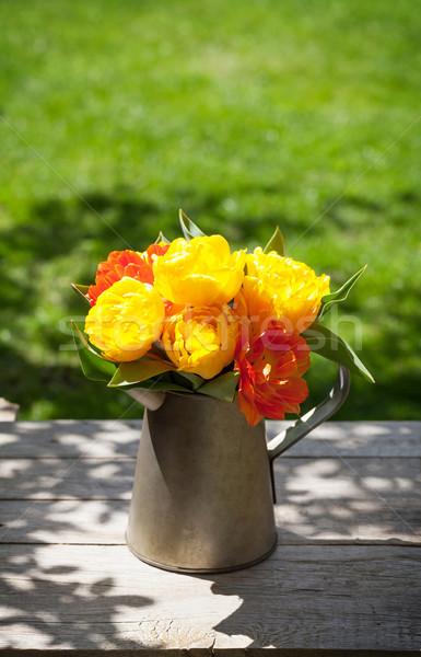 Színes tulipánok virágcsokor locsolókanna napos kert Stock fotó © karandaev