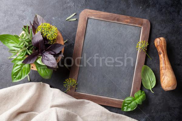 Garden herbs in mortar and blackboard Stock photo © karandaev
