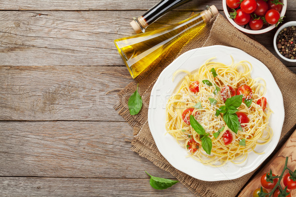 Espaguete macarrão tomates salsa mesa de madeira topo Foto stock © karandaev