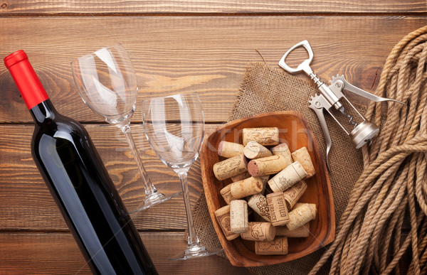 Red wine bottle, wine glasses, bowl with corks and corkscrew Stock photo © karandaev