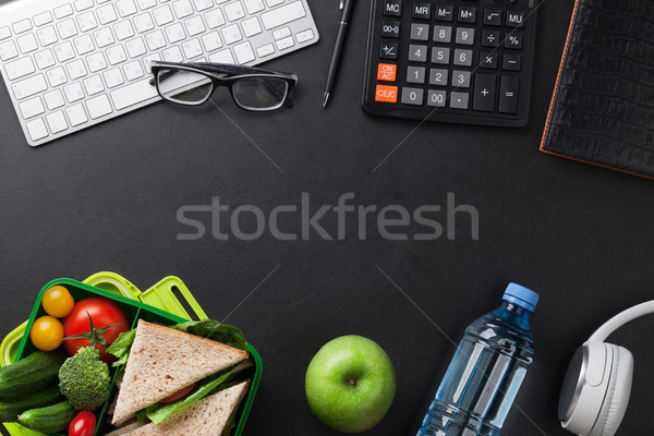 Office desk with supplies and lunch box Stock photo © karandaev