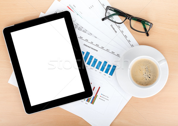 Coffee cup, tablet over papers with numbers and charts Stock photo © karandaev