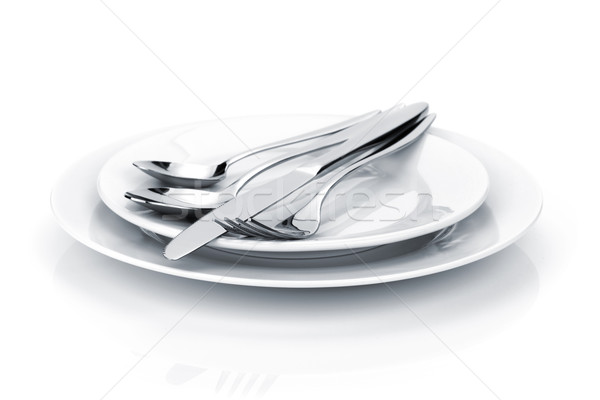 Silverware or flatware set of fork, spoons and knife on plates Stock photo © karandaev