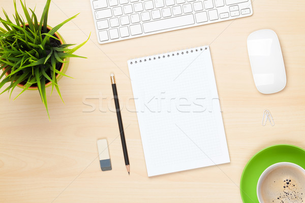 Office table with notepad, computer, coffee cup and flower Stock photo © karandaev