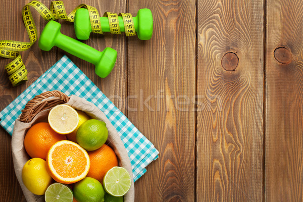 Stock photo: Citrus fruits in basket and dumbells. Oranges, limes and lemons