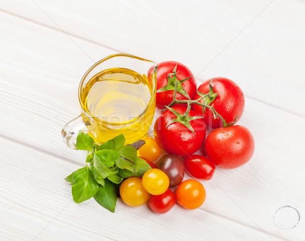 Olive oil, tomatoes, basil on wooden table Stock photo © karandaev