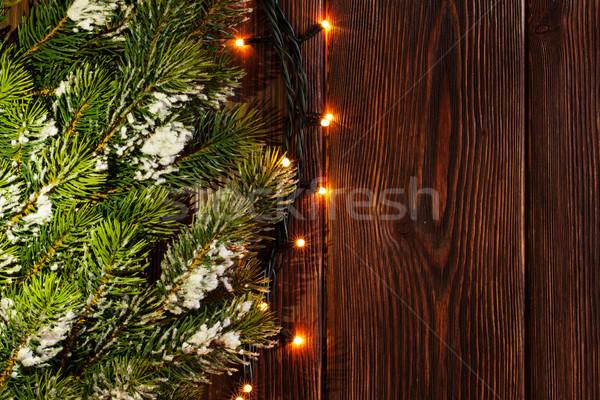 Christmas tree branch and lights on wood Stock photo © karandaev