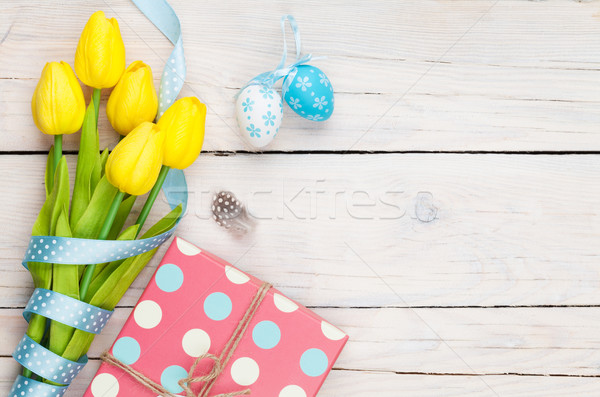 Easter background with blue and white eggs, yellow tulips and gi Stock photo © karandaev