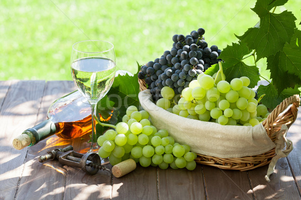 White wine bottle and glass, red and white grape Stock photo © karandaev