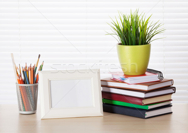 Workplace with photo frame, pencils, books Stock photo © karandaev