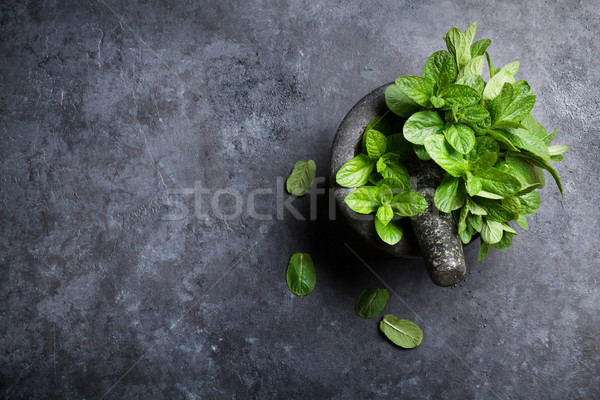 Fresh mint leaves in mortar on stone table Stock photo © karandaev