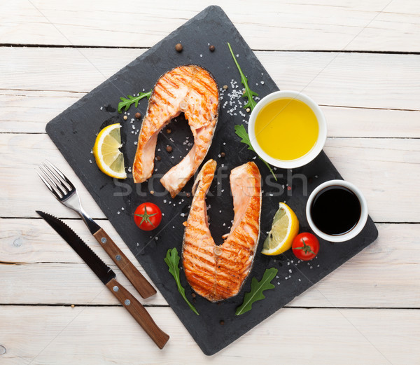 Grilled salmon, salad and condiments on wooden table Stock photo © karandaev